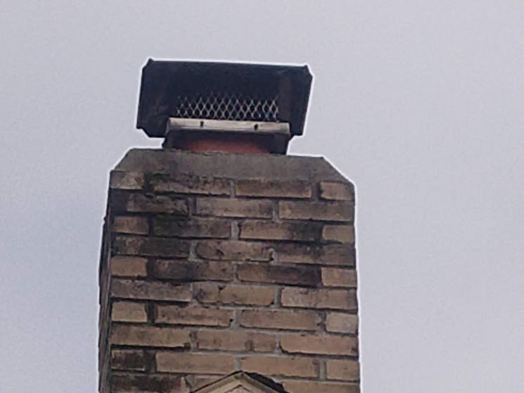 Rain cap mounted on a terra cotta flue tile with rounded corners.
