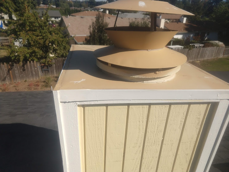 "Wood exterior chimney ""chase"" of a ""zero-clearance"" chimney/fireplace system."