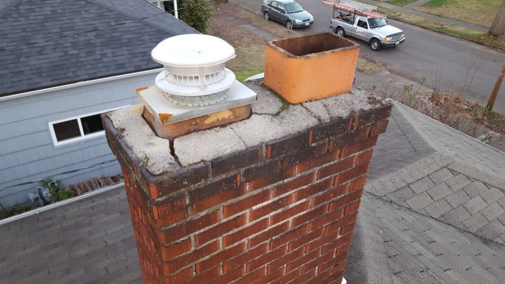 Loose and deteriorated chimney cap. Can be easily removed.
